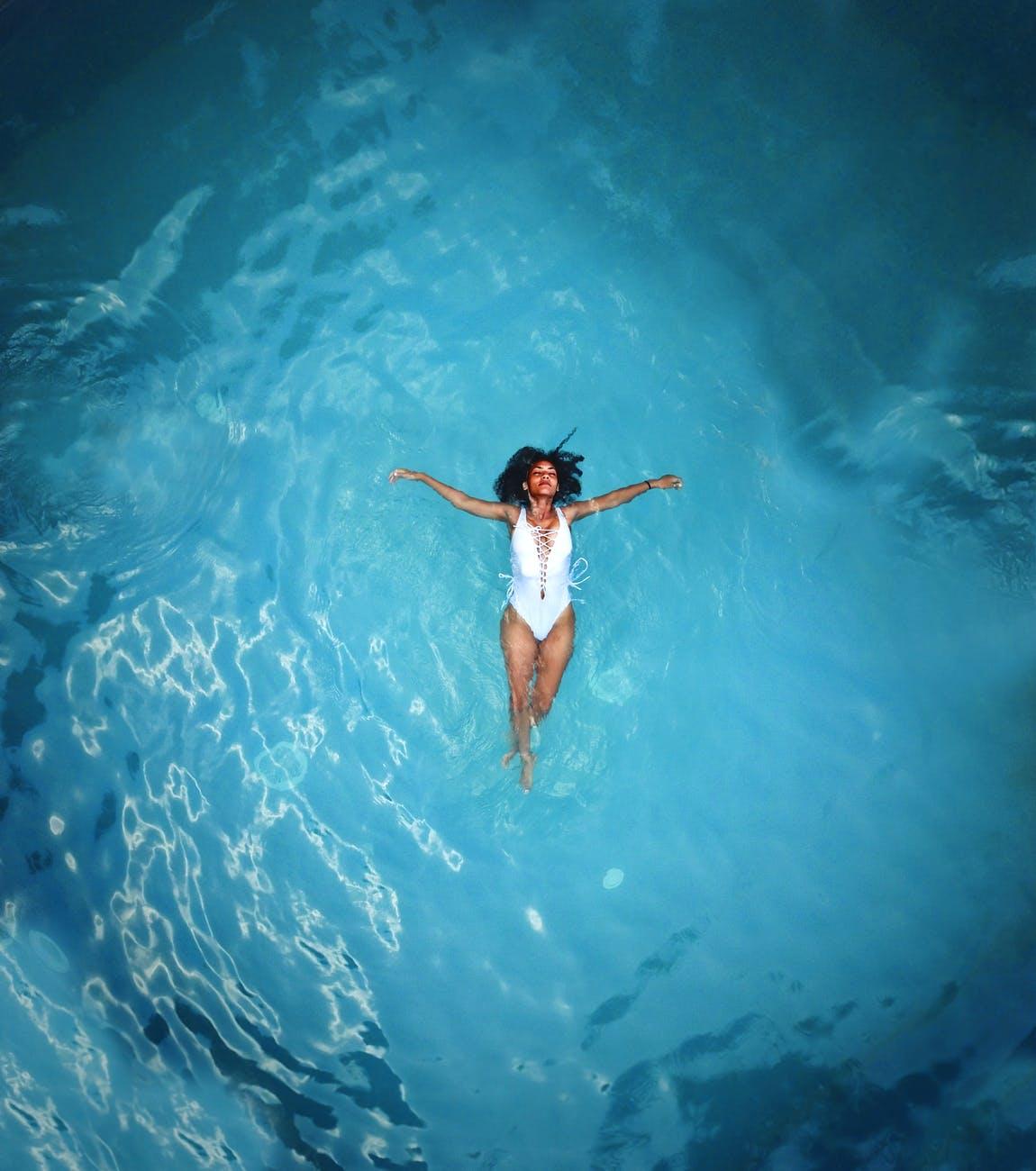 woman in white monokini swimming on body of water